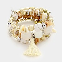 Beaded coil bracelet with tassel